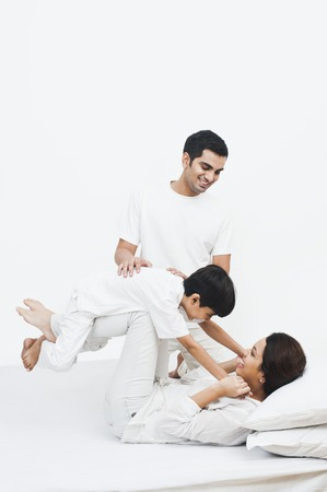 행복 한 부모는 침대에 자신의 아들과 함께 연주