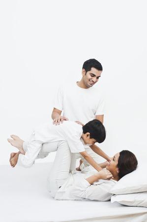 Genitori felici giocando con il loro figlio sul letto Archivio Fotografico - 24698197