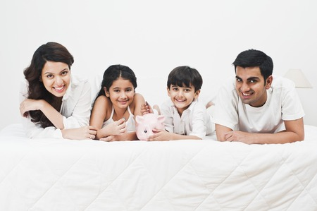 Happy family with a piggy bank on the bed