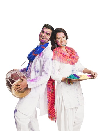 holi: Couple celebrating Holi with colors and a drum