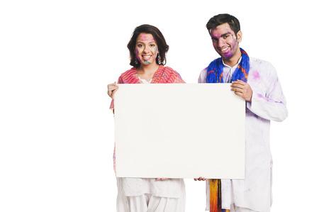 Couple celebrating Holi and holding a blank placard photo