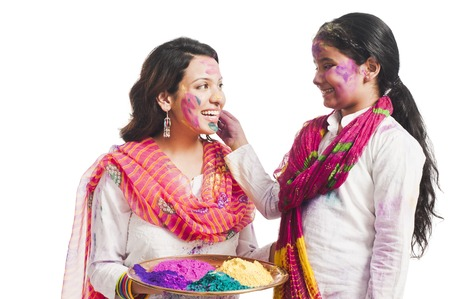 Woman celebrating Holi festival with her daughter