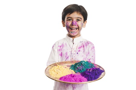 Boy holding Holi colors in a plate photo