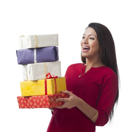 Happy woman holding stack of gifts and smiling Stock Photo