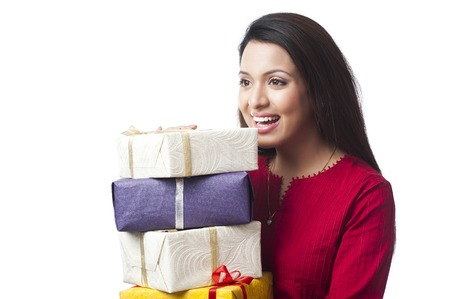 Close-up of a happy woman holding a stack of gifts