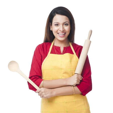 Portrait of a woman holding a rolling pin and ladle