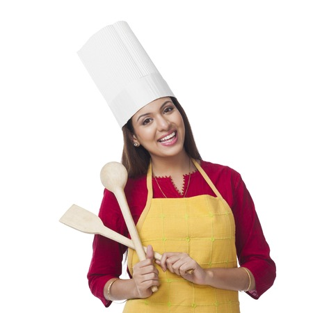 indian subcontinent ethnicity: Portrait of a happy woman holding a spatula and ladle Stock Photo