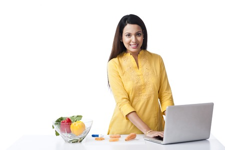 Woman using a laptop in a kitchen and smiling photo