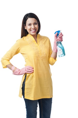 Woman spraying with a cleaning fluid photo