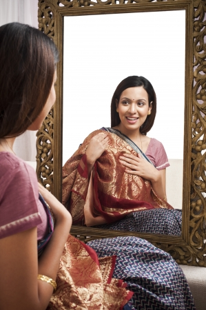 Reflection of a woman in mirror trying a sari on herself photo