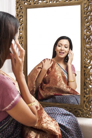 traditionally indian: Reflection of a woman in mirror trying a sari on herself and talking on a mobile phone