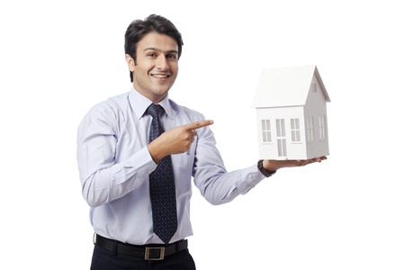 model home: Businessman pointing towards a model home