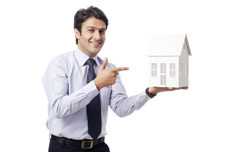 Businessman pointing towards a model home photo