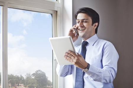 Businessman using digital tablet and talking on a cell phone photo