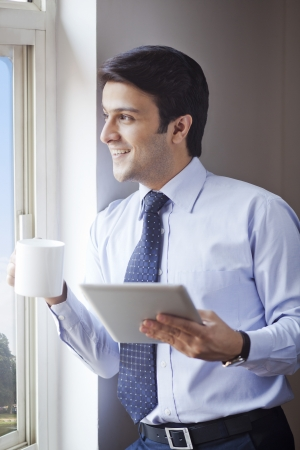 Businessman holding a digital tablet with a cup of coffee at window photo