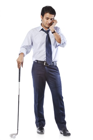 Businessman holding a golf club and talking on cell phone photo