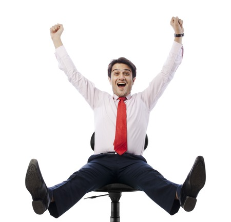 Businessman sitting on an office chair and looking excited photo