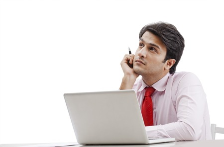 Businessman thinking in front of a laptop photo
