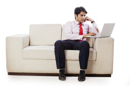 couch: Businessman sitting on a couch and working on a laptop