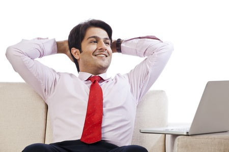 Businessman sitting on a couch and looking cheerful in front of a laptop photo