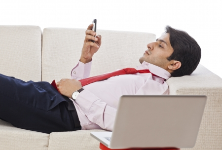 clipping  messaging: Businessman lying on a couch and using a mobile phone