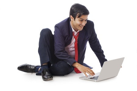 Businessman working on a laptop and smiling photo