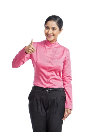 Portrait of a businesswoman showing thumbs up sign photo