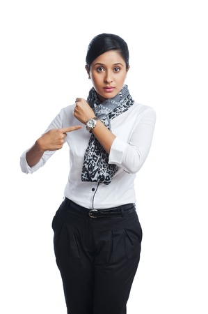 getting late: Businesswoman pointing toward a wristwatch Stock Photo