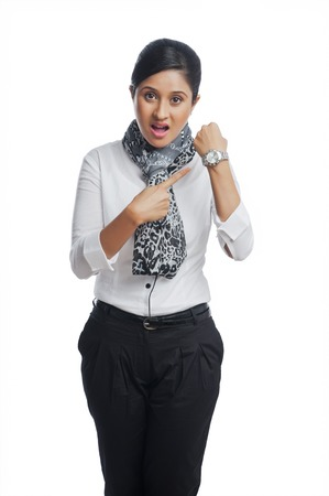 getting late: Businesswoman shouting and pointing toward a wristwatch