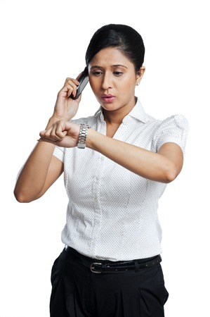 getting late: Businesswoman checking the time while talking on a mobile phone