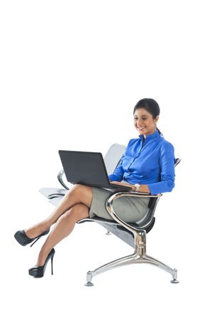 Businesswoman sitting on a bench and using a laptop photo