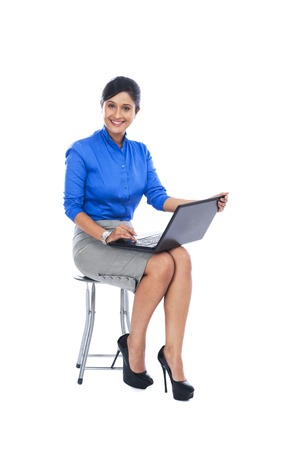 stool: Businesswoman smiling while sitting on a stool and using a laptop Stock Photo