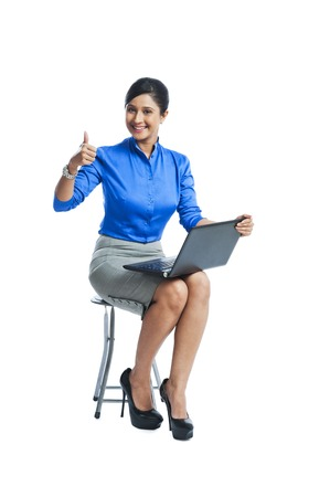 Businesswoman showing thumbs up sign while sitting on a stool and using a laptop photo