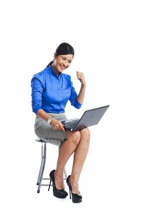 Businesswoman looking excited while sitting on a stool and using a laptop photo