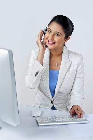 Female customer service representative using a desktop pc photo