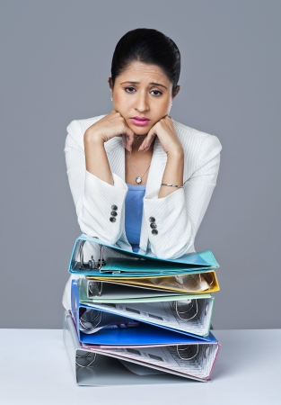 Businesswoman leaning on a stack of files and looking worried Banco de Imagens