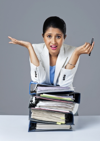 Businesswoman leaning on a stack of files and looking upset photo