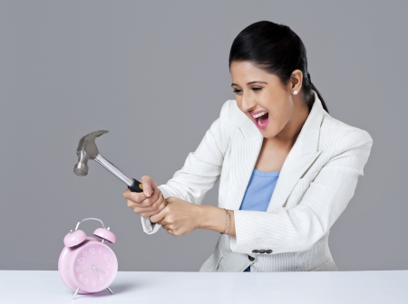 Businesswoman smashing alarm clock with hammer photo