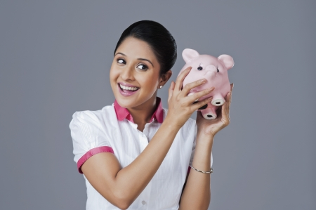 Woman shaking a piggy bank photo