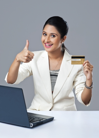 Businesswoman holding a credit card and showing thumbs up sign photo