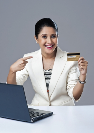 Portrait of a businesswoman pointing towards a credit card photo