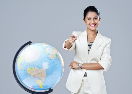 Businesswoman pointing towards a globe and smiling photo