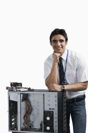 Engineering student standing with a computer cabinet photo
