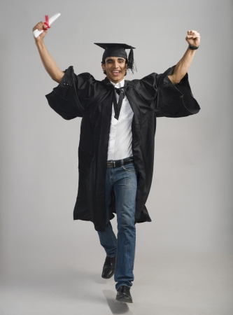 indian subcontinent ethnicity: Male graduate cheering with his diploma