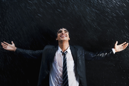 Businessman enjoying in the rain photo
