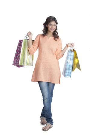 Woman carrying shopping bags and smiling photo