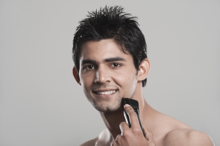 Portrait of a man shaving with electric razor