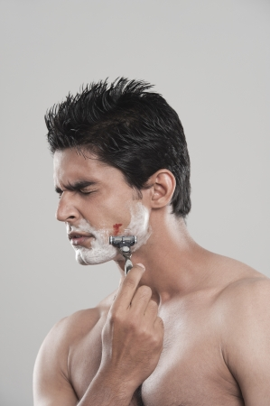 Man with shaving cut with painful expression on face