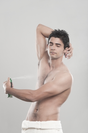 Man applying deodorant over his body photo