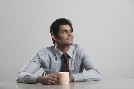 Businessman lost in thoughts while drinking coffee photo